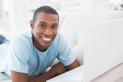 Smiling Afro man with laptop lying on sofa Stock Photography