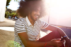 Smiling afro man sitting outside with cell phone Royalty Free Stock Image