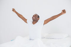 Smiling Afro man stretching his arms out in bed Stock Image