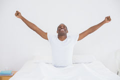 Smiling Afro man stretching his arms out in bed Stock Photo