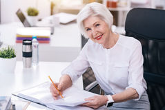 Smiling aged business lady performing her responsibilities in the office stock photo