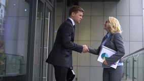 Smiling aged business woman meeting young male employee, partners shaking hands stock video footage
