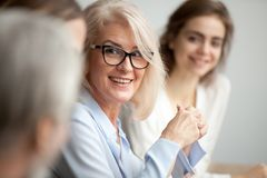 Smiling aged businesswoman looking listening to colleague at tea. Smiling aged businesswoman in glasses looking at colleague at team meeting, happy attentive Stock Photo
