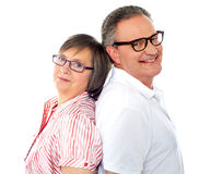Smiling aged couple posing back to back Stock Photo