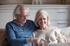 Happy aged couple have fun watching video on laptop royalty free stock image