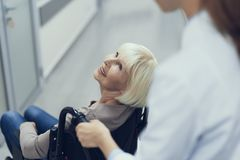 Smiling aged lady on pushchair is enjoying medic assistance royalty free stock images