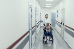 Happy woman on wheelchair is enjoying doctor assistance. Smiling aged lady is using pushchair for moving hospital. Caring practitioner is helping her by stock photography
