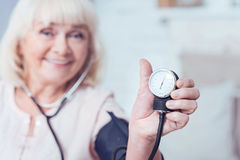 Smiling aged lady using tonometer at home. Look at this. Skilled delighted old woman sitting at home and measuring blood pressure while expressing positivity royalty free stock images