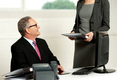 Smiling aged male boss looking at secretary. While she presents business file to him Stock Photos