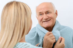 Smiling aged man is being wrapped in blanket Royalty Free Stock Photo