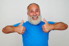 Smiling aged man giving two thumbs up against white background. Smiling bearded aged man in bright blue T-shirt is giving two thumbs up isolated against white Stock Photo