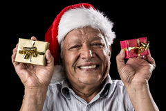 Smiling Aged Man Holding Two Small Xmas Gifts. Venerable man brimming over with a smile. He is wearing a Kris Kringle hat. Holding up a small wrapped gift in Stock Images