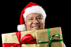 Smiling Aged Man Peeking Across Two Golden Gifts. Smiling male senior peeping across two foot-long gifts that cover his chest and chin. Both presents wrapped Royalty Free Stock Photos