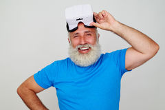 Smiling aged man satisfied by work of virtual reality headset Stock Image