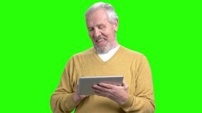 Smiling aged man using digital tablet. Cheerful man working on computer tablet on Alpha Channel backgroud. Elderly people and technology concept stock footage
