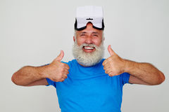 Smiling aged man in VR-headset on his head giving two thumbs up. Smiling bearded aged man in VR-headset on his head is giving two thumbs up isolated on white Stock Photos