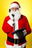 Smiling aged Santa attending phone call royalty free stock photos