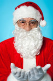 Smiling aged Santa posing with open palms Stock Photos