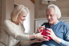 Smiling aged wife making surprise presenting gift to husband stock photo