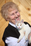 Smiling aged woman with cat on hands Stock Images