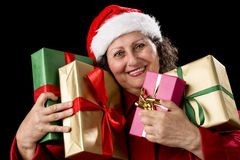 Smiling Aged Woman Embracing Four Wrapped Gifts. Elderly female with Santa Claus cap and red coat is hugging four wrapped Christmas presents. Gifts are green Stock Image