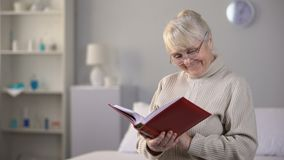 Smiling aged woman in eyeglasses watching photo album, fond memories, family. Stock footage stock footage