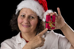 Smiling Aged Woman Holding and Pointing at Red Gift. Gentle middle-aged woman wearing a Santa Claus hat. She is pointing at a small red Christmas present that Royalty Free Stock Photo
