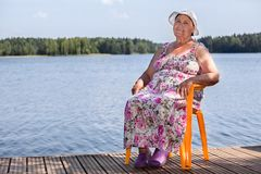 Smiling aged woman sitting on wooden pier at lake, copyspace Royalty Free Stock Images
