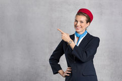 Smiling air hostess showing Royalty Free Stock Photography