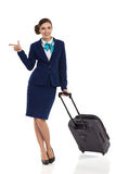 Smiling Air Stewardess With Trolley Bag Pointing Royalty Free Stock Photo