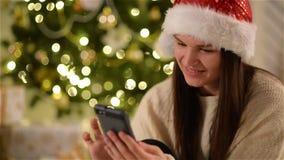 Smiling Amazed Woman in Santa Hat Using Gadget Sitting Next to Christmas Tree. Joyful Girl with Long Dark Hair Touching stock video footage