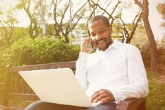 Smiling american african businessman in informal clothes working at sunny street on laptop,checking e-mail. Man using stock image