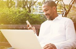 Smiling american african businessman in informal clothes working at sunny street on laptop and smartphone for calling. Friends via social networks Royalty Free Stock Photos