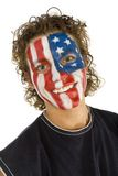 Smiling American supporter. Portrait of young smailing fan with painted The USA flag on face. He's looking at camera. Front view royalty free stock images
