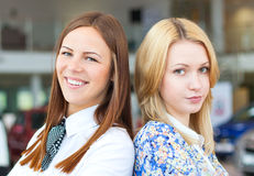 Smiling ang angry business women. In car service Royalty Free Stock Photo