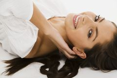 Smiling angel. Beautiful smiling girl in white lies on the white clothes Stock Image