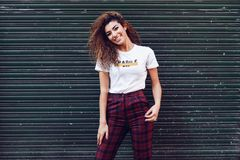 Smiling arab girl in casual clothes in the street. stock photos