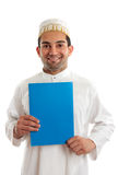 Smiling arab man with brochure. Arab italian mixed race business man holding a brochure or document.  Bohra men wear a traditional white three piece outfit, plus Stock Image