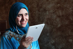 Smiling arab muslim woman with mobile and headset Royalty Free Stock Photo