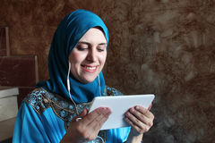 Smiling arab muslim woman with mobile and headset Royalty Free Stock Image