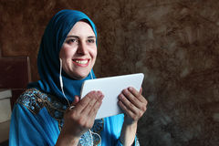 Smiling arab muslim woman with mobile and headset Royalty Free Stock Photos