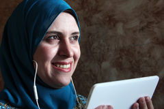 Smiling arab muslim woman with mobile and headset Royalty Free Stock Images