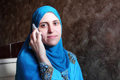 Smiling arab muslim woman with mobile Royalty Free Stock Photos