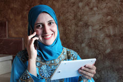 Smiling arab muslim woman with mobile Royalty Free Stock Photography