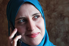 Smiling arab muslim woman with mobile Stock Image