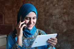 Smiling arab muslim woman with mobile and tablet Stock Photo