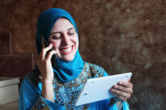 Smiling arab muslim woman with mobile and tablet Stock Image