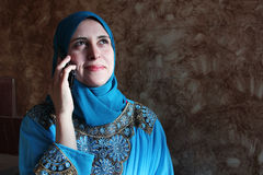 Smiling arab muslim woman with mobile and tablet Stock Images