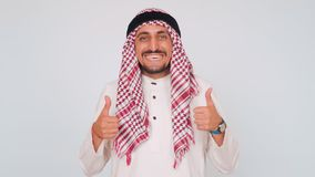 Smiling Arab in national dress shows fingers of both hands up. The man smiles widely. Business and office. Arab works in stock video footage