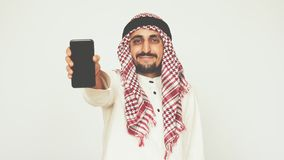Smiling Arab in national dress shows smartphone and smiles widely. A man shows a modern phone. Business and office. Arab stock footage